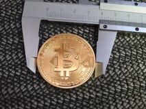 Golden Bitcoin and vernier caliper. Royalty Free Stock Photo