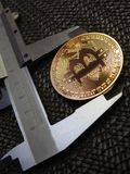 Golden Bitcoin and vernier caliper. Royalty Free Stock Images