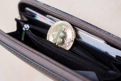 A golden bitcoin in a wallet stock photo