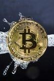 Golden bitcoin and water splash. Money laundering. Golden bitcoin and water splash on dark background. Money laundering, enrichment and profit concept Stock Photos