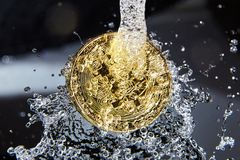 Golden bitcoin and water splash. Money laundering. Golden bitcoin and water splash on dark background. Money laundering, enrichment and profit concept Royalty Free Stock Photo