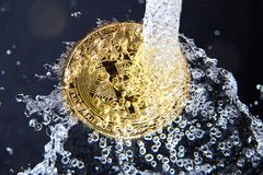 Golden bitcoin and water splash. Money laundering. Golden bitcoin and water splash on dark background. Money laundering, enrichment and profit concept Stock Image