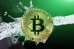 Golden bitcoin and water splash. Money laundering. Golden bitcoin and water splash on dark background. Money laundering, enrichment and profit concept Stock Images