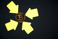 Golden bitcoin with yellow paper arrows on the black background. stock photos