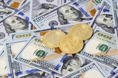 Golden Bitcoins on American dollars Royalty Free Stock Images
