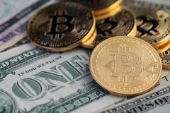 Golden Bitcoins and banknotes of one dollar. Bitcoins on US dollars royalty free stock photography