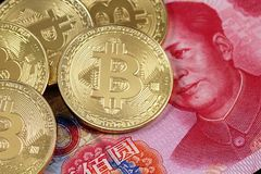 Golden bitcoins close up with a 100 yuan note Royalty Free Stock Photography