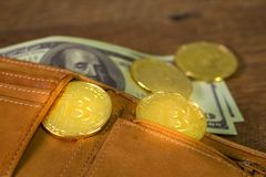 Golden bitcoins Crypto currency in brown leather wallet with US Dollar bill royalty free stock photos