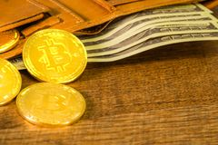 Golden bitcoins Crypto currency in brown leather wallet with US Dollar bill on wooden royalty free stock images