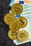 Golden bitcoins and euro banknotes. stock photos