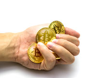 Golden bitcoins in hand. Digital symbol of a new virtual currency on white background. Golden bitcoins in hand. Digital symbol of a new virtual currency Royalty Free Stock Photography