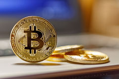 Golden bitcoins on the laptop touchpad closeup. Cryptocurrency virtual money Stock Photo