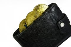 Golden bitcoins lie in black leather wallet closeup. On white bckground Royalty Free Stock Photos
