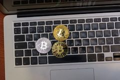 Golden bitcoins lies on silver notebook keyboard Royalty Free Stock Images