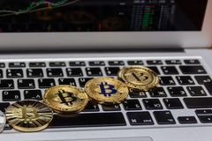 Golden bitcoins lies on silver notebook keyboard Stock Images