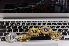 Golden bitcoins lies on silver notebook keyboard Stock Image