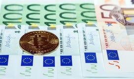 Golden bitcoins is a monetary denominations of 100 and 50 euros. bussines concept. Golden bitcoins is a monetary denominations of 100 and 50 euros royalty free stock photos
