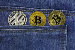 Golden bitcoins and silver litecoin lie back pocket of blue jeans closeup stock image