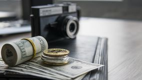Golden bitcoins on a top of other coins and on the us dollars bill with a photo camera on a backgroung. Freelancer stock photos