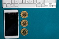 Golden bitcoins on a top, and smart phone and laptop. Bitcoin cryptocurrency. Miner with dollars from trading. Digital currency. Profit from mining Stock Photos