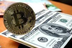 Golden Bitcoins on US dollars. Digital currency close-up. Crypto currency top view. Real coins of bitcoin on banknotes of one stock image