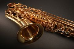 Golden on black. Shiny golden saxophone on black background Royalty Free Stock Photos