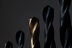 Golden and Black Drill Bits on dark background Royalty Free Stock Photos