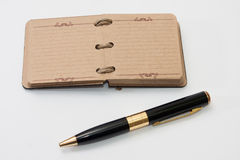 Golden black pencil with antique notebook Royalty Free Stock Photos