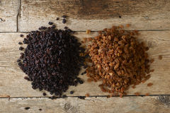 Golden and black raisins over wooden table Stock Images