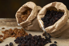 Golden and black raisins in paper bags on a wooden table Royalty Free Stock Photo