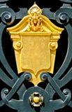 Golden blazon. Ornament decoration over iron fence royalty free stock photo