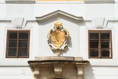 Golden blazon. Golden noble blazon with crown on grey wall between windows Stock Photos