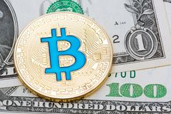 Golden blue bitcoin on different dollar banknotes background. Stock Photos