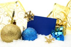 Golden and blue christmas decoration on snow with wishes card. Decoration of golden and blue christmas baubles and gifts with ribbon with wishes card on snow Stock Image