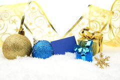 Golden and blue christmas decoration on snow with wishes card. Decoration of golden and blue christmas baubles and gifts with ribbon with wishes card on snow Stock Photography
