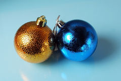 Golden and blue christmass balls on a glass background Stock Photos