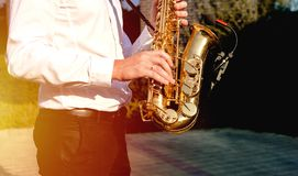 Golden Blues. Boys Band saxophone section at event , jazz player male playing on Saxophone, music instrument played by man saxopho. Nist player musician at  folk royalty free stock photography