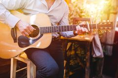 Guitar with a man`s male hands playing the guitar on wooden wall background, electric or acoustic guitar with nature light. Concep stock photo