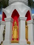 Golden Boddhisattva. Red and white stupa with golden bodhisattva images at a temple in Phetchaburi, Thailand Stock Photos