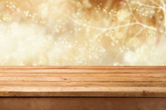 Golden bokeh background with empty wooden table for product montage display stock photography
