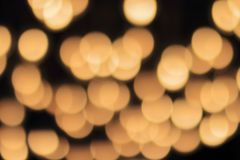 Golden bokeh on a black background, abstract dark backdrop with defocused warm lights.  Royalty Free Stock Image