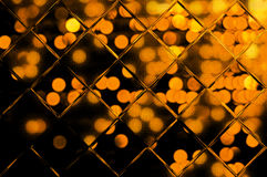 Golden bokeh on black behind glass Royalty Free Stock Photography