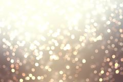 Golden bokeh on champagne color background. Festive sparkles abstract texture. royalty free stock images