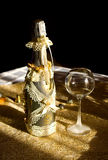 Golden bottle champaign and empty goblet. Golden bottle bottle champaign with decoration and empty goblet Royalty Free Stock Image