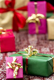 Golden Bow Around Green Gift. Green gift box between other plain-colored presents wrapped in magenta, gold and red. Tight close-up shot with shallow depth of Stock Images