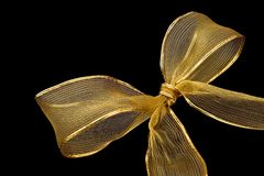 Golden bow isolated. Golden ribbon and bow isolated on black background stock photo