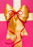 Golden bow made from silk on pink Royalty Free Stock Photography