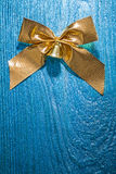 Golden bow on old painted wooden board Stock Photos