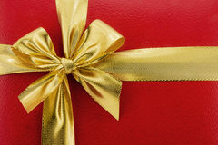 Golden bow on a red background (holiday background) Royalty Free Stock Photography