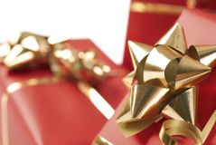Golden bow on red present. A closeup view of a bow of gold ribbon on a Christmas gift wrapped in red paper stock photo